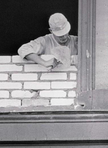 Восточноберлинский рабочий заделывает окно, выходящее на Западный Берлин